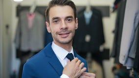 Χαμογελώντας άτομο που φορά το κοστούμι στο κατάστημα του ράφτη ιματισμού απόθεμα βίντεο