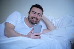Χαμογελώντας άτομο που χρησιμοποιεί το έξυπνος-τηλέφωνό του που βρίσκεται στο κρεβάτι στοκ εικόνα