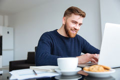 Χαμογελώντας άτομο που χρησιμοποιεί το φορητό προσωπικό υπολογιστή στο σπίτι Στοκ Φωτογραφίες