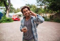 Χαμογελώντας άτομο στα ακουστικά που ακούει τη μουσική από το τηλέφωνο κυττάρων Στοκ Φωτογραφία