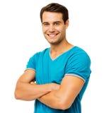 Χαμογελώντας άτομο στα μόνιμα όπλα μπλουζών που διασχίζονται Στοκ φωτογραφία με δικαίωμα ελεύθερης χρήσης