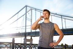 Χαμογελώντας άτομο στην αθλητική ομοιόμορφη ομιλία στο κινητό τηλέφωνο Στοκ φωτογραφία με δικαίωμα ελεύθερης χρήσης