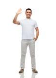 Χαμογελώντας άτομο στο κενό άσπρο κυματίζοντας χέρι μπλουζών στοκ εικόνες