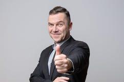 Χαμογελώντας άτομο στο κοστούμι με τον αντίχειρα επάνω Στοκ Φωτογραφίες