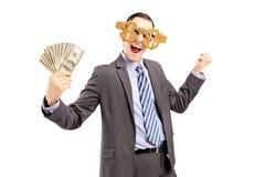 Χαμογελώντας άτομο στο κοστούμι που φορά τα γυαλιά και το κράτημα δολαρίων των δολαρίων στοκ φωτογραφίες