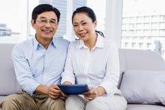 Χαμογελώντας άτομο στο σπίτι στον καναπέ Στοκ εικόνα με δικαίωμα ελεύθερης χρήσης