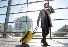 Χαμογελώντας άτομο ταξιδιού που περπατά και που μιλά στο κινητό τηλέφωνο Στοκ εικόνες με δικαίωμα ελεύθερης χρήσης