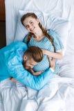 Χαμογελώντας έγκυος γυναίκα με το σύζυγο που αγκαλιάζει την κοιλιά στο νοσοκομείο Στοκ Φωτογραφίες