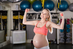 Χαμογελώντας έγκυος γυναίκα που αυξάνει τα χέρια με τα βάρη στη γυμναστική στοκ φωτογραφία με δικαίωμα ελεύθερης χρήσης