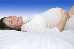 Χαμογελώντας έγκυος μητέρα στο άσπρο ξάπλωμα λωρίδων Στοκ Φωτογραφία