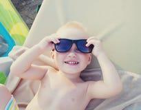 Χαμογελώντας αγόρι με τα γυαλιά στην παραλία Στοκ εικόνα με δικαίωμα ελεύθερης χρήσης