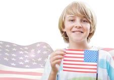 Χαμογελώντας αγόρι που κρατά μια αμερικανική σημαία ενάντια στην κυματίζοντας αμερικανική σημαία Στοκ Εικόνες