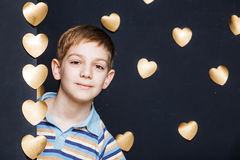 Χαμογελώντας αγόρι που κρυφοκοιτάζει στο χρυσό υπόβαθρο καρδιών Στοκ φωτογραφία με δικαίωμα ελεύθερης χρήσης