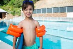 Χαμογελώντας αγόρι που στέκεται με το kickboard και armband στο poolside Στοκ εικόνες με δικαίωμα ελεύθερης χρήσης