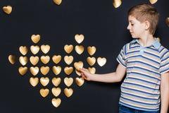 Χαμογελώντας αγόρι που συγκεντρώνει τη μεγάλη χρυσή καρδιά στο σκοτεινό υπόβαθρο Στοκ Φωτογραφία