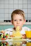 Χαμογελώντας αγόρι που τρώει τα μακαρόνια και το κράτημα του δικράνου Στοκ φωτογραφίες με δικαίωμα ελεύθερης χρήσης