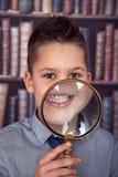 Χαμογελώντας αγόρι, πρώτος-γκρέιντερ με μια ενίσχυση - γυαλί Στοκ Φωτογραφία