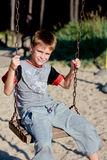 Χαμογελώντας αγόρι στην ταλάντευση Στοκ Εικόνες