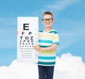 Χαμογελώντας αγόρι eyeglasses με το λευκό κενό πίνακα Στοκ Φωτογραφία