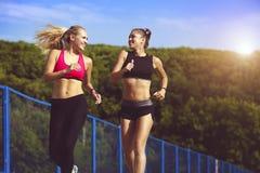 Χαμογελώντας αθλητικά κορίτσια σε ένα τρέξιμο στο πάρκο Υγιής τρόπος ζωής Στοκ Φωτογραφίες