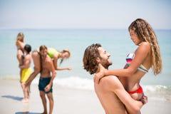Χαμογελώντας ανυψωτική γυναίκα νεαρών άνδρων στην παραλία Στοκ Φωτογραφίες