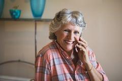 Χαμογελώντας ανώτερη γυναίκα που μιλά στο τηλέφωνο στο σπίτι στοκ φωτογραφίες με δικαίωμα ελεύθερης χρήσης