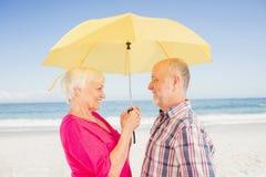 Χαμογελώντας ανώτερη ομπρέλα εκμετάλλευσης ζευγών Στοκ φωτογραφία με δικαίωμα ελεύθερης χρήσης
