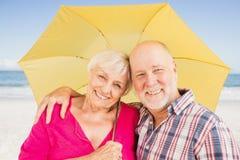 Χαμογελώντας ανώτερη ομπρέλα εκμετάλλευσης ζευγών Στοκ Εικόνα