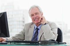 Χαμογελώντας ανώτερος διευθυντής που συνεργάζεται με ένα όργανο ελέγχου Στοκ Φωτογραφία