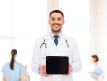 Χαμογελώντας αρσενικός γιατρός με το PC ταμπλετών Στοκ φωτογραφία με δικαίωμα ελεύθερης χρήσης
