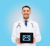 Χαμογελώντας αρσενικός γιατρός με το PC ταμπλετών Στοκ Εικόνες