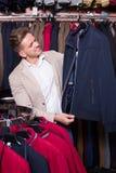 Χαμογελώντας αρσενικός πελάτης που εξετάζει τα παλτά Στοκ φωτογραφία με δικαίωμα ελεύθερης χρήσης