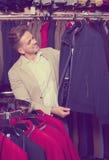 Χαμογελώντας αρσενικός πελάτης που εξετάζει τα παλτά Στοκ εικόνες με δικαίωμα ελεύθερης χρήσης