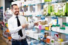 Χαμογελώντας αρσενικός πελάτης που ψάχνει τη σωστή ιατρική Στοκ φωτογραφίες με δικαίωμα ελεύθερης χρήσης
