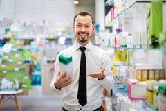 Χαμογελώντας αρσενικός πελάτης που ψάχνει τη σωστή ιατρική Στοκ Εικόνες