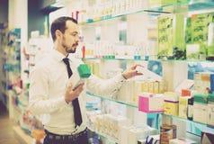 Χαμογελώντας αρσενικός πελάτης που ψάχνει τη σωστή ιατρική Στοκ Φωτογραφίες