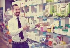 Χαμογελώντας αρσενικός πελάτης που ψάχνει τη σωστή ιατρική Στοκ Φωτογραφία