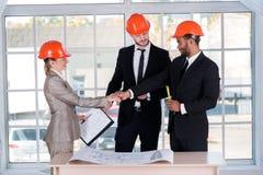Χαμογελώντας αρχιτέκτονες επιχειρηματιών που τινάζουν τα χέρια Επιχειρηματίας τρία Στοκ Φωτογραφία