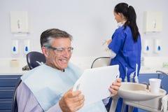 Χαμογελώντας ασθενής που κρατά έναν καθρέφτη Στοκ εικόνα με δικαίωμα ελεύθερης χρήσης