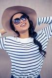 Χαμογελώντας ασιατική γυναίκα με το καπέλο και τα γυαλιά ηλίου Στοκ Εικόνες
