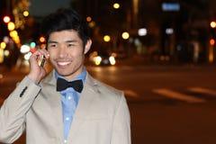 Χαμογελώντας ασιατικός επιχειρηματίας που καλεί τηλεφωνικώς στην οδό τη νύχτα - εικόνα αποθεμάτων Στοκ εικόνα με δικαίωμα ελεύθερης χρήσης