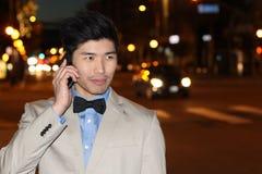 Χαμογελώντας ασιατικός επιχειρηματίας που καλεί τηλεφωνικώς στην οδό τη νύχτα - εικόνα αποθεμάτων Στοκ Εικόνες