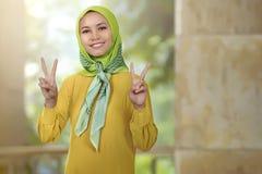 Χαμογελώντας ασιατικό κορίτσι γυναικών με το hijab που παρουσιάζει σημάδι ειρήνης Στοκ φωτογραφίες με δικαίωμα ελεύθερης χρήσης