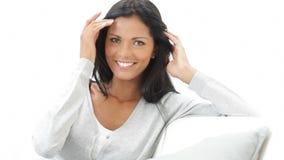 Χαμογελώντας λατινική γυναίκα στον καναπέ απόθεμα βίντεο