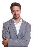 Χαμογελώντας λατινικός επιχειρηματίας στο γκρίζο κοστούμι με τα διασχισμένα όπλα στοκ εικόνες