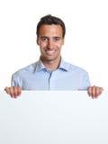 Χαμογελώντας λατινικό άτομο με μια πινακίδα για τη διαφήμιση στοκ φωτογραφία με δικαίωμα ελεύθερης χρήσης
