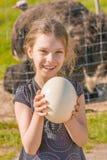 Χαμογελώντας αυγό στρουθοκαμήλων εκμετάλλευσης κοριτσιών στοκ φωτογραφίες