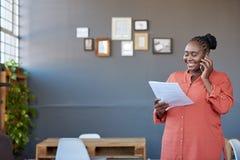 Χαμογελώντας αφρικανική επιχειρηματίας που μιλά σε ένα κινητό τηλέφωνο και την ανάγνωση της γραφικής εργασίας Στοκ εικόνα με δικαίωμα ελεύθερης χρήσης
