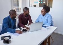 Χαμογελώντας αφρικανικοί συνάδελφοι που χρησιμοποιούν ένα lap-top μαζί σε ένα γραφείο Στοκ Εικόνα