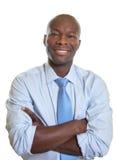 Χαμογελώντας αφρικανικός επιχειρηματίας με τα διασχισμένους όπλα και το δεσμό Στοκ Εικόνες